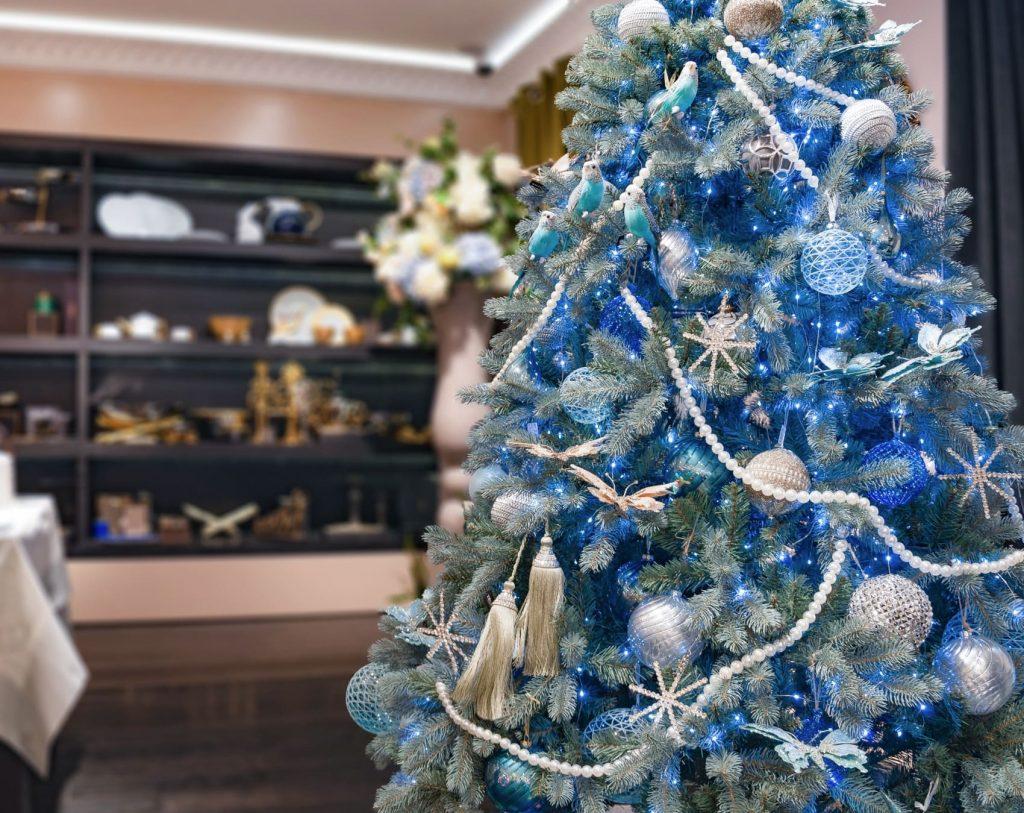 Украшенная искусственная голубая ель с гиряндами и шарами